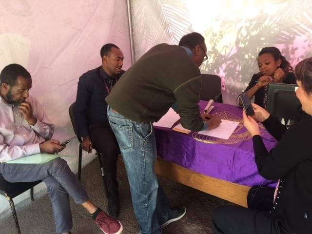 Opening a CBE Birr account at a street-side promotional tent. Photo credit: Strategic Impact Advisors.